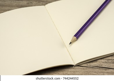 Close up shot of an empty notebook and pencil