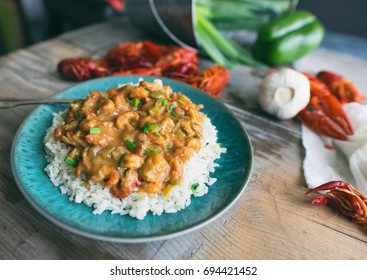 Close up shot of etouffee made from crayfish or crawfish over rice on a turquoise blue plate.