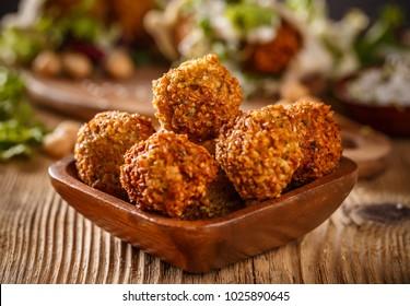 Close up shot of falafel balls in wooden bowl