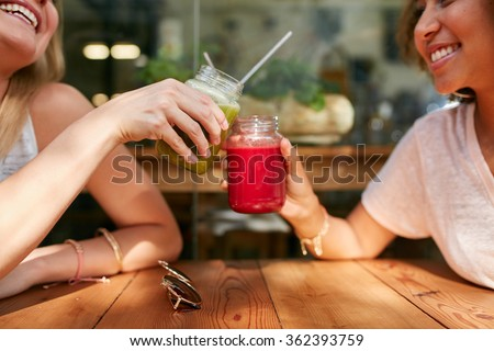Close up shot of female friends toasting juice glasses at sidewalk cafe. Two happy women enjoying fresh drinks at outdoor coffee shop.