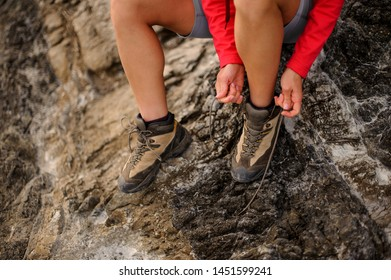 Close shot of female hiker tiyng up shoelaces in hiking boots and sitting on rock