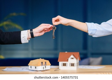 Close up shot of female realtor hands giving keys from the new flat, house to female clients.