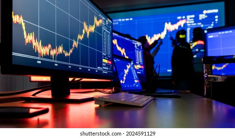 Close up shot of financial analysis graph chart stock exchange bitcoin cryptocurrency report on computer screen monitors and laptop on working in trading room while broker meeting in shadow behind.