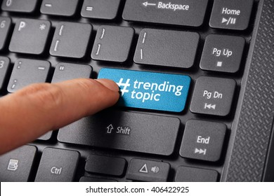 Close up shot of a finger clicking the TRENDING TOPIC button on a laptop keyboard