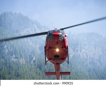Close up shot of a fire helicopter fighting a forest fire with the pilot looking down watching as he fills his water bladder on a hot sunny day