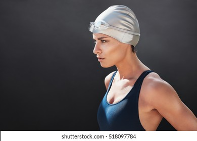 Close up shot of fit young woman in swimming costume looking away on black background. Female swimmer looking focused before her workout.