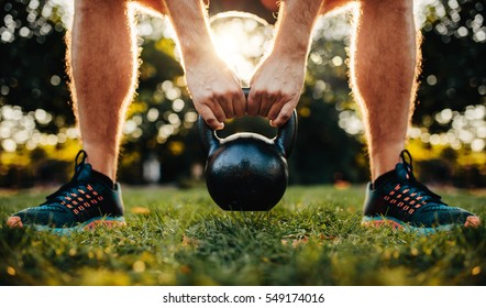 Close up shot of fitness man working out with kettlebell in the park, focus on hands holding kettle bell on grass.