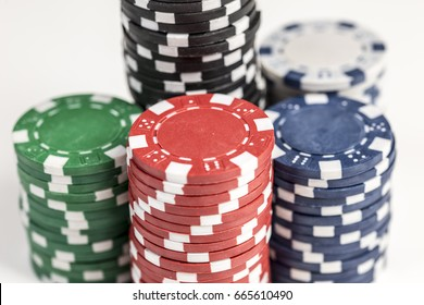 Close up shot of five piles of different coloured gaming chips isolated against a white background