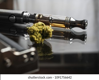 Close up shot and focus on the cartridge of vape pen in the background and real cannabis or weed with roller is blurred in the foreground and text space on the right under the dark theme