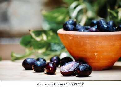 Close up shot of fresh Jamun fruit in bowl on wooden table.