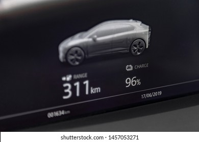 Close up shot of fully electric car dashboard trip computer display showing the status of the battery and available range in kilometers