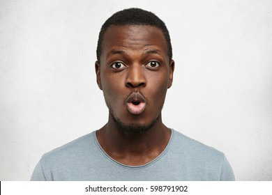 Close up shot of funny young African American man dressed casually pouting lips and raising brows, expressing shock or surprise, posing against white wall background with copy space for your text