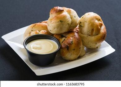 Close up shot of garlic knots with dipping sauce