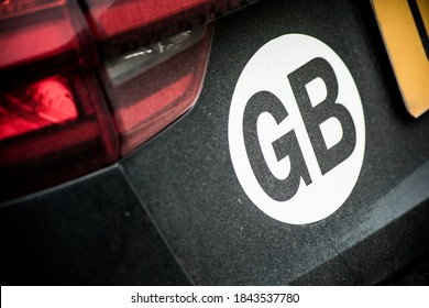 A close up shot of a GB country designation sticker on the rear of a black car. Nice clear focus on the sticker, car is slightly dirty, with the numberplate creeping into the frame.