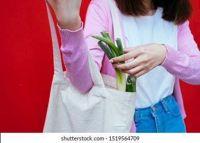 Close up shot of a girl checking the leek in her canvas bag infront of the red wall.