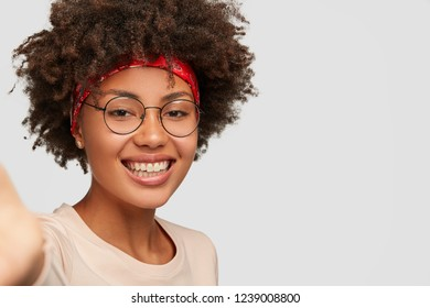 Close up shot glad feminine girl has toothy smile, Afro hairstyle, beautiful clean skin, wears transparent glasses, stretches hand as holds unrecognizable device, makes selfie over white background