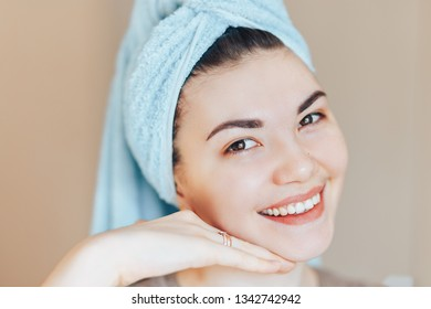 Close up shot of glad satisfied woman being happy after spa procedure, has fresh soft healthy skin, broad smile, white perfect teeth touch her face look at camera close up selected focus