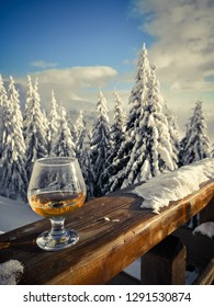 Close up shot of a glass of alcohol backed by some trees with snow.