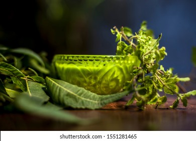 Close up shot of glass bowl full of tulsi or basil and neem or Indian lilac paste in it along with fresh neem and tulsi leaves on a brown wooden surface.