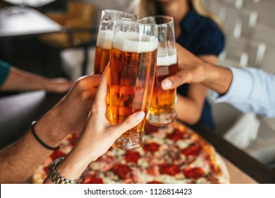 Close up shot of glasses of beer and pizza