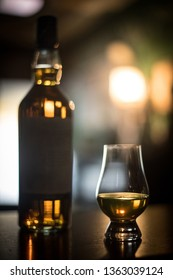 Close up shot of a Glencairn whisky glass and a bottle.