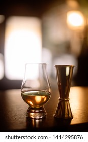 Close up shot of a Glencairn whisky glass and a jigger.