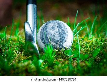A CLOSE UP SHOT OF A GOLF CLUB BEHIND A GOLF BALL WITH A BEN FRANKLIN 100 DOLLAR BILL SEEN THROUGH THE CLEAR COVER ON A GREEN FAIRWAY.  GOLF IS A VERY EXPENSIVE SPORT.