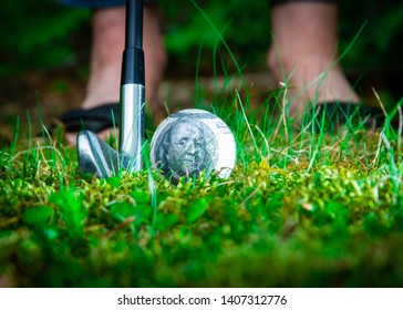 A close up shot of a golf club behind a golf ball with on a green fairway with feet out of focus in the background.  The golf ball is transparent and has a 100 dollar bill inside,  Golf is expensive.