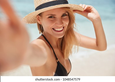 Close up shot of good looking female tourist enjoys free time outdoor near ocean on beach, looks at camera during leisure on sunny summer day, poses for selfie. Happy smiling tourist in tropics