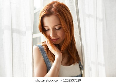 Close up shot of gorgeous tender young European red haired female with cute freckles posing at window between transparent curtains, looking down with shy smile, touching her loose ginger hair