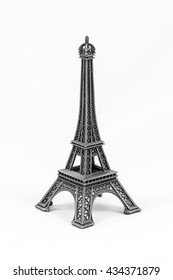 Close up shot of a gray miniature model of the Eiffel Tower isolated on a white background