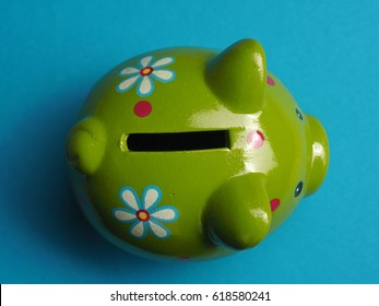 Close up shot of a green cute ceramic piggy bank, view from above, financial money savings concept