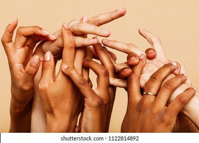 Close up shot of a group of hands  reaching up and holding on to each other