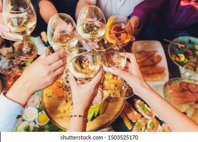 Cerca de un grupo de personas tomando copas con vino o champán frente a los antecedentes del bokeh. manos de personas mayores