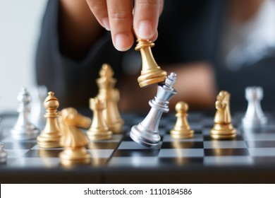 Close up shot hand of business woman moving golden chess to defeat and kill silver king chess on white and black chess board for business challenge competition winner and loser concept, selective focu