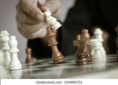 Close up shot hand of business woman playing the chess board to win by killing the king of opponent metaphor business competition winner and loser select focus shallow depth of field vintage tone