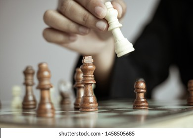 Close up shot hand of business woman playing the chess board to win by killing the king of opponent metaphor business competition winner and loser select focus shallow depth of field with vintage tone