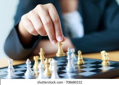 Close up shot hand of business woman moving golden chess to defeat a silver king chess on white and black chess board for business challenge competition winner and loser concept, selective focus