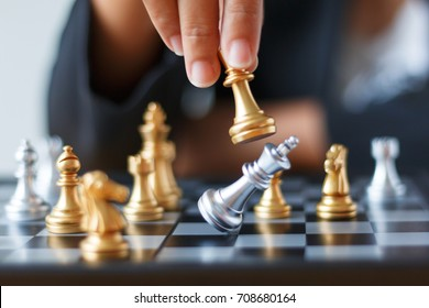 Close up shot hand of business woman moving golden chess to defeat and kill silver king chess on white and black chess board for business challenge competition winner and loser concept, selective