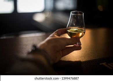 Close up shot of a hand grabbing a Glencairn whisky glass.