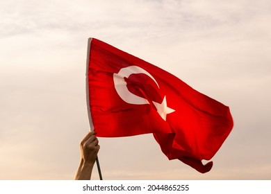 Close up shot of a hand held Turkish flag waving on a warm cloudy sky.