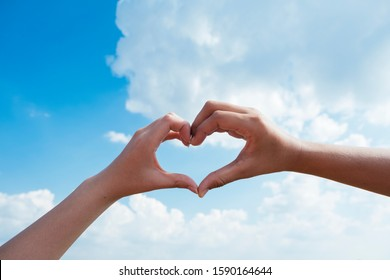 close up shot of hand make a heart shape with blue sky and clod.