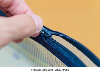 A close up shot of a hand pulling open the zipper of a small plastic pouch.