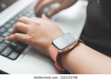Close up shot of hand wearing smart watch using laptop