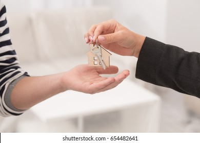 Close up shot of hands giving keys of an apartment. Woman hand passing keys to new owners.