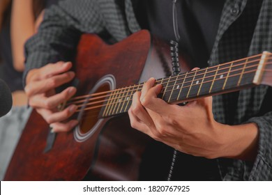 Close up shot hands of guitarist perform with his acustic guitar