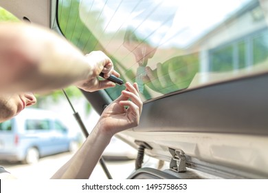 Close up shot hands of man removing old car window film