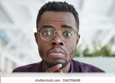 Close up shot of handsome African Americam male with dark pure skin, wears round spectacles and formal clothes listens attentively his experienced colleague who teaches how make presentation