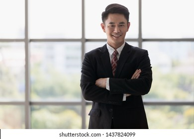 Close up shot of handsome Asian businessman in black suit standing and crossed his arm by confident feel.