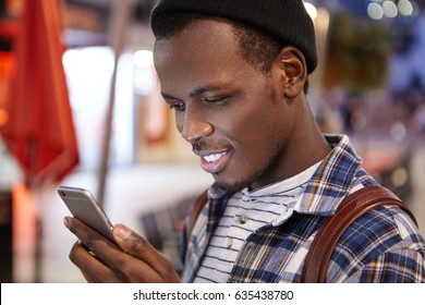Close up shot of handsome bearded young dark-skinned hipster carrying backpack on his shoulders reading messages online via social networks, using 3G or 4g internet connection on his mobile